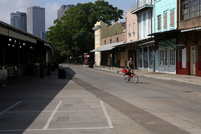 A woman rides her bike through the empty French Market in the French Quarter neighborhood, following the outbreak of the coronavirus disease (COVID-19), in New Orleans