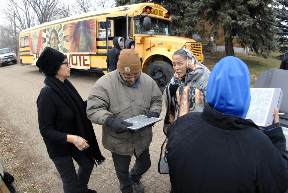 FILE - In this Tuesday, Nov. 6, 2018 file photo Judith LeBlanc, left, with Four Directions, a non-profit voting equality organization for Native Americans, helps local volunteers before going door-to-door looking for voters in Selfridge, N.D., and offering a free bus ride to the polling precinct. On Friday, Aug. 23, 2019, The Associated Press reported on stories circulating online incorrectly asserting that a court upheld a North Dakota law stripping voting rights from Native Americans. They are still eligible to vote in the state. A change to North Dakota's voter ID law, however, has been criticized for potentially suppressing Native American votes. (Mike McCleary/The Bismarck Tribune via AP)