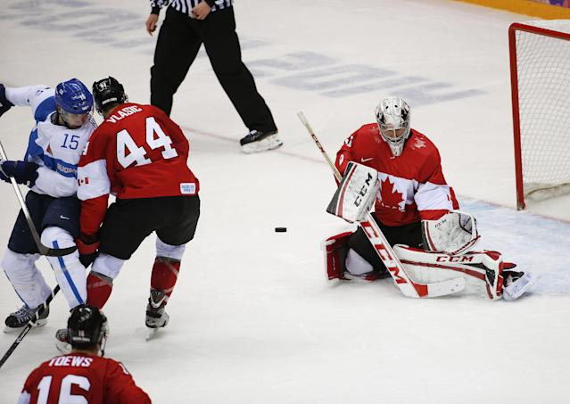 Finland forward Tuomo Ruutu, far left, redirects the puck past Canada goaltender Carey Price and into the net for a goal during the second period of a men's ice hockey game at the 2014 Winter Olympics, Sunday, Feb. 16, 2014, in Sochi, Russia. (AP Photo/Julio Cortez)