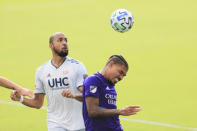 Orlando City midfielder Junior Urso (11) heads the ball in front of New England Revolution forward Teal Bunbury (10) during the first half of an MLS playoff soccer match, Sunday, Nov. 29, 2020, in Orlando, Fla. (AP Photo/Matt Stamey)