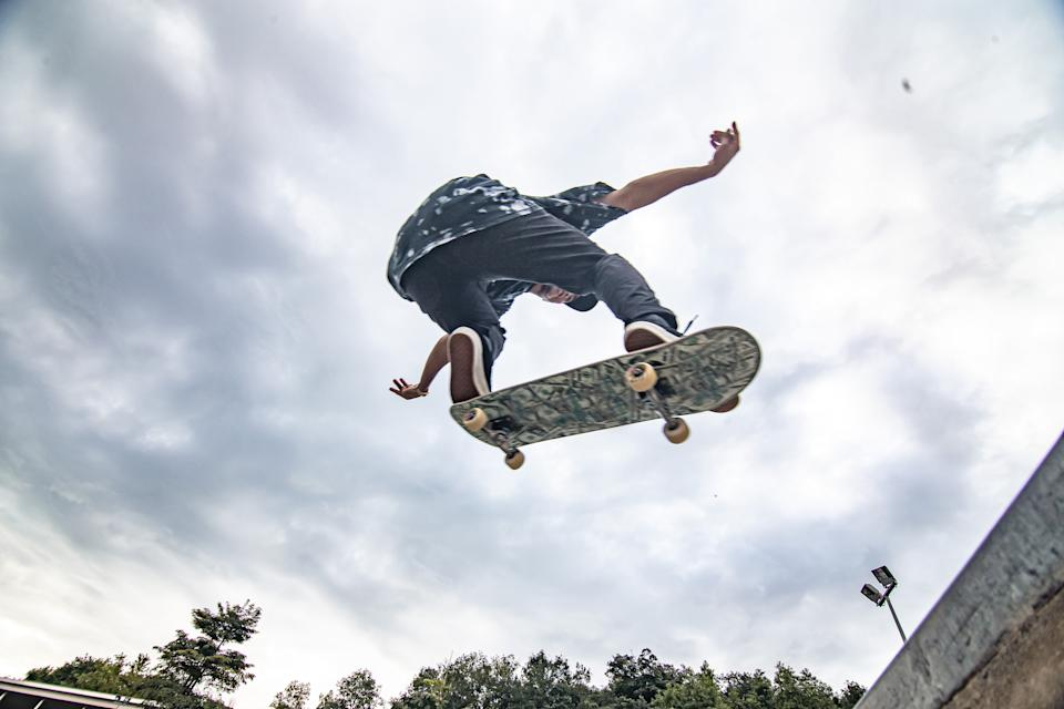 Asian skateboarder in action jump in the air