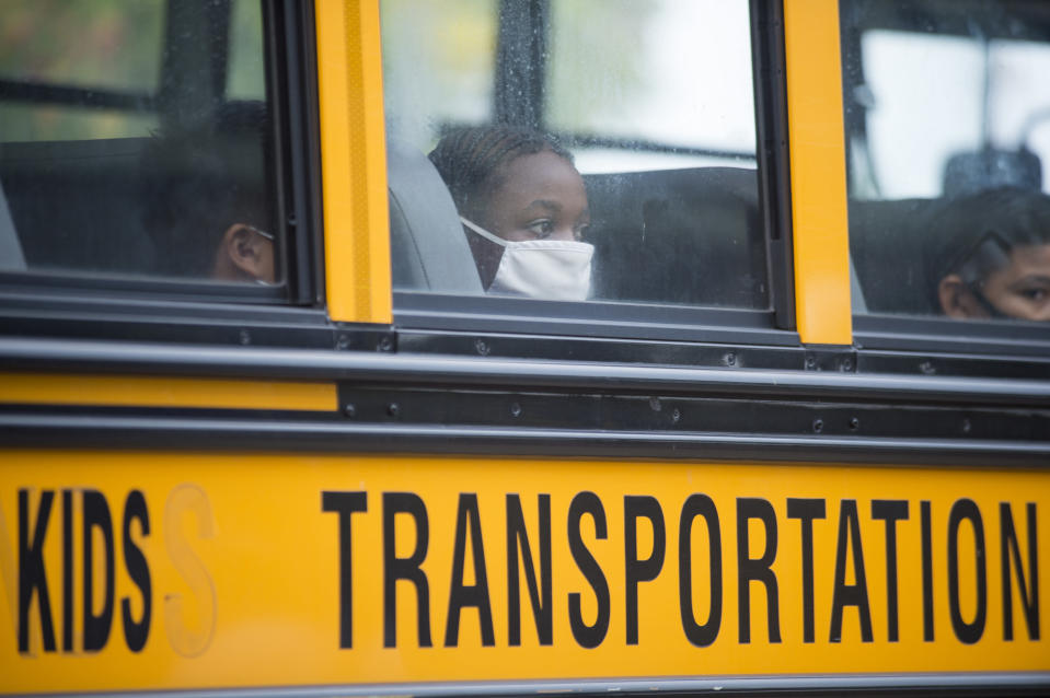 FILE - In this Oct. 12, 2020, file photo, students arrive by bus at Foundation Preparatory School for their return to school during the coronavirus in New Orleans. With COVID-19 cases soaring nationwide, school districts across the U.S. are yet again confronting the realities of a polarized country and the lingering pandemic as they navigate mask requirements, vaccine rules and social distancing requirements for the fast-approaching new school year. (Chris Granger/The Times-Picayune/The New Orleans Advocate via AP, File)