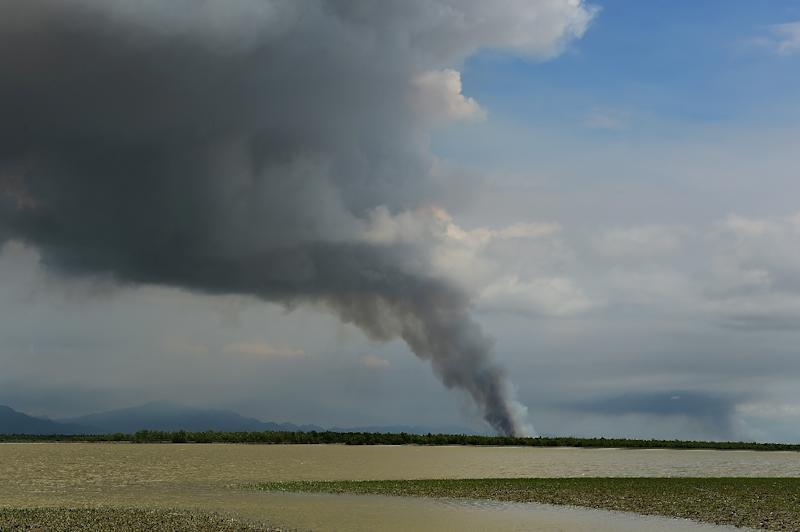 Smoke billows from a fire in an area in Myanmar's Rakhine state as seen from the Bangladeshi shore of the Naf river on September 14, 2017 (AFP Photo/Munir UZ ZAMAN)