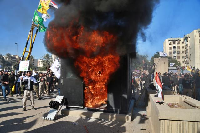 Protesters burn property in front of the U.S. Embassy in Baghdad on Dec. 31. (Photo: Khalid Mohammed/AP)