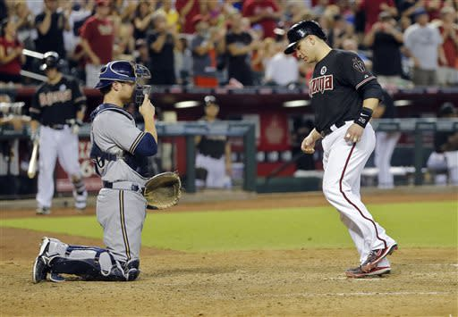 Arizona Diamondbacks' Miguel Montero, right, walks in the go-ahead run after teammate Eric Chavez drew a bases-loaded walk against the Milwaukee Brewers during the seventh inning of a baseball game, Saturday, July 13, 2013, in Phoenix. At left is Brewers catcher Jonathan Lucroy. (AP Photo/Matt York)
