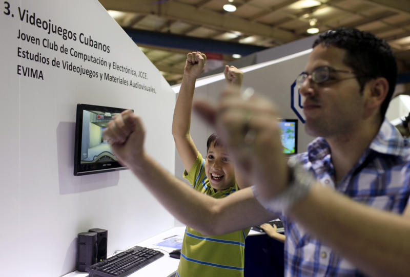 "In this March 22, 2013 photo, Rogelio Garcia, 10, left, and Luis Macias, 20, celebrate as they play the video game, ""Gesta Final"" - which translates roughly as ""Final Heroic Deed,"" at a technology fair in Havana, Cuba. Island programmers have unveiled the brand new 3-D shoot-'em-up video game that puts a distinctly Cuban twist on gaming, letting players recreate decisive clashes from the 1959 revolution and giving youngsters a taste of the uprising in which many of their grandparents fought. (AP Photo/Franklin Reyes)"