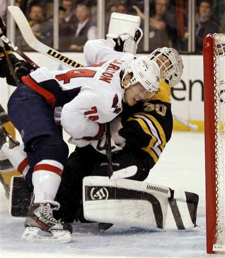 Washington Capitals defenseman John Carlson runs into Boston Bruins goalie Tim Thomas during the first period of Game 5 in a first-round NHL Stanley Cup playoff hockey series in Boston Saturday, April 21, 2012. Carlson received a penalty on the play. (AP Photo/Winslow Townson)