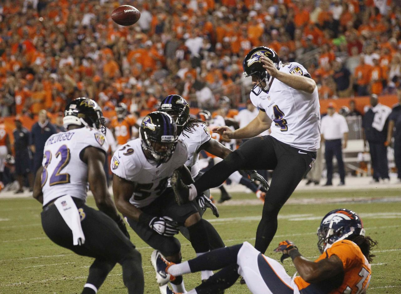 Denver Broncos' David Bruton (30) blocks a punt by Baltimore Ravens' Sam Koch (4) during their NFL football game in Denver, Colorado September 5, 2013. REUTERS/Rick Wilking (UNITED STATES - Tags: SPORT FOOTBALL)