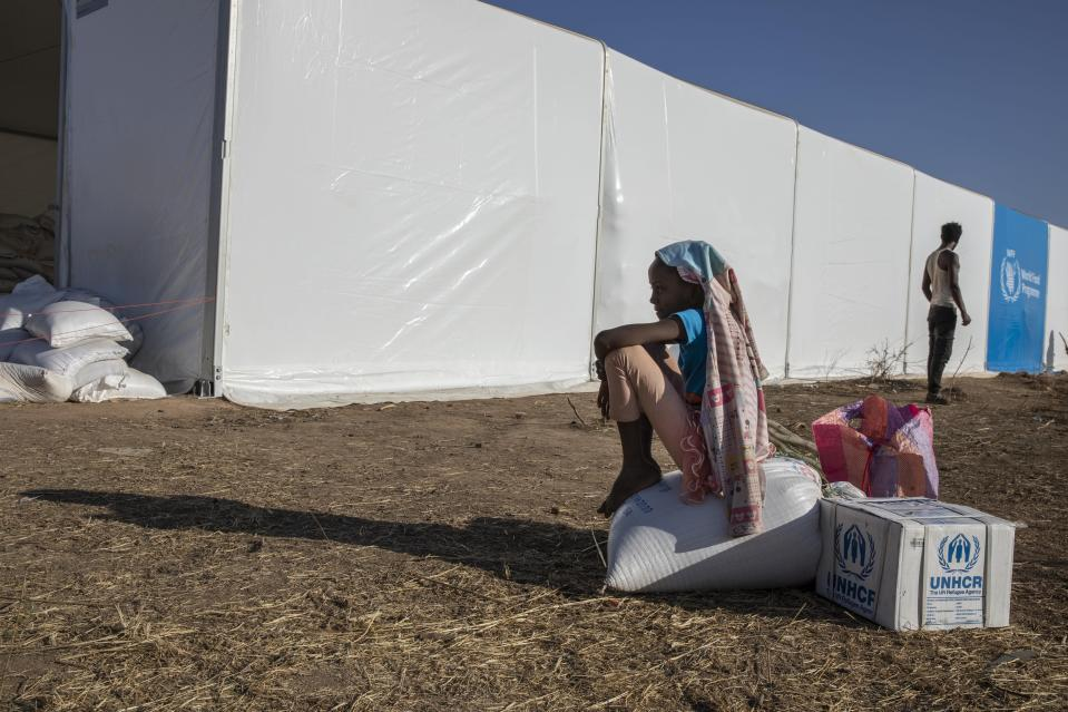 A Tigray refugee girl who fled the conflict in Ethiopia's Tigray region, sits on aid she received from the UNHCR and WFP at Umm Rakouba refugee camp in Qadarif, eastern Sudan, Tuesday, Nov. 24, 2020. (AP Photo/Nariman El-Mofty)