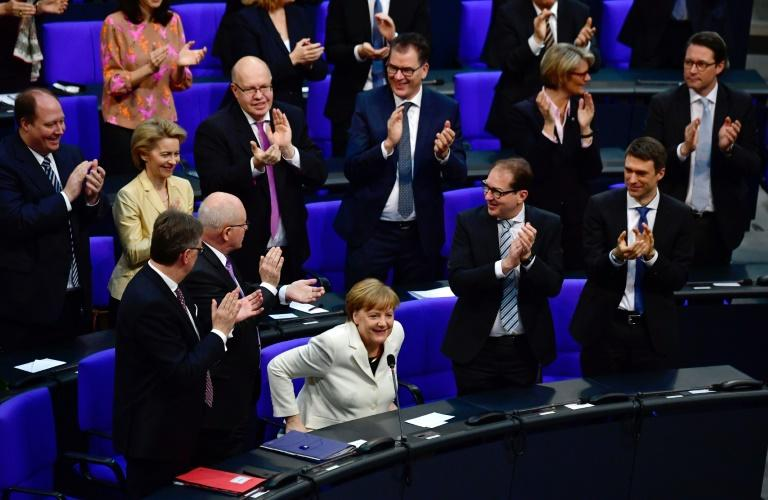Lawmakers in Berlin's glass-domed Reichstag voted 364-315 with nine abstentions for Merkel