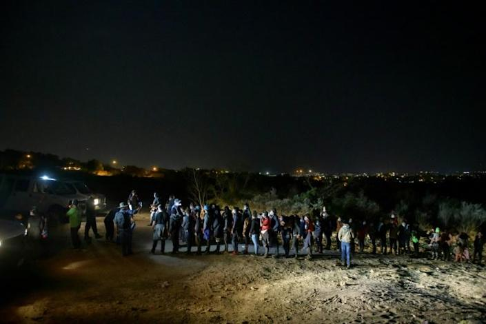 Undocumented immigrants who have crossed the Rio Grande from Mexico to the United States line up in front of Customs and Border Patrol in 2021