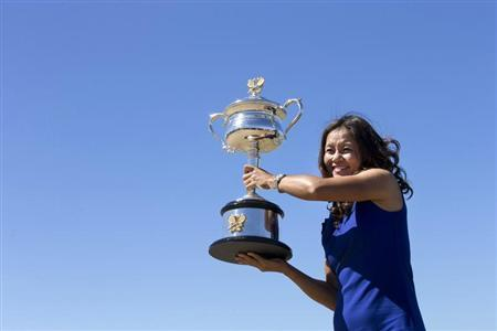 Li Na of China poses with her Australian Open trophy during a photo call in Melbourne