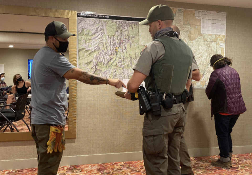 Search crew members and police are seen talking in front of a map of the park.