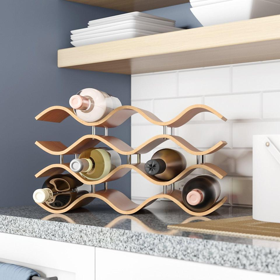 <p>This <span>Ivy Bronx Chesney 10 Bottle Tabletop Wine Bottle Rack</span> ($99) will make a wavy addition to your kitchen counter.</p>