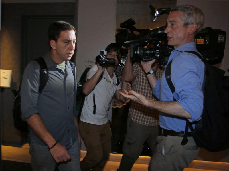 Glenn Greenwald, left, a reporter for The Guardian, walks out from his hotel room in Hong Kong Monday, June 10, 2013. Greenwald spoke to media about his interview with Edward Snowden, the 29-year-old contractor who allowed himself to be revealed as the source of disclosures about the U.S. government's secret surveillance programs. (AP Photo/Vincent Yu)