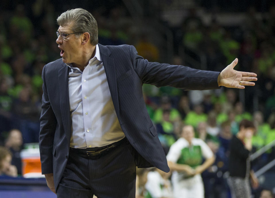 Geno Auriemma with his hand out in front of fans in green T-shirts in the stands.