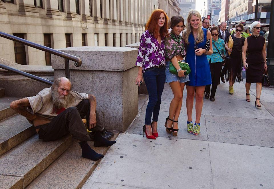 <p>2012. Three young women pose next to a homeless man during New York Fashion Week.</p>