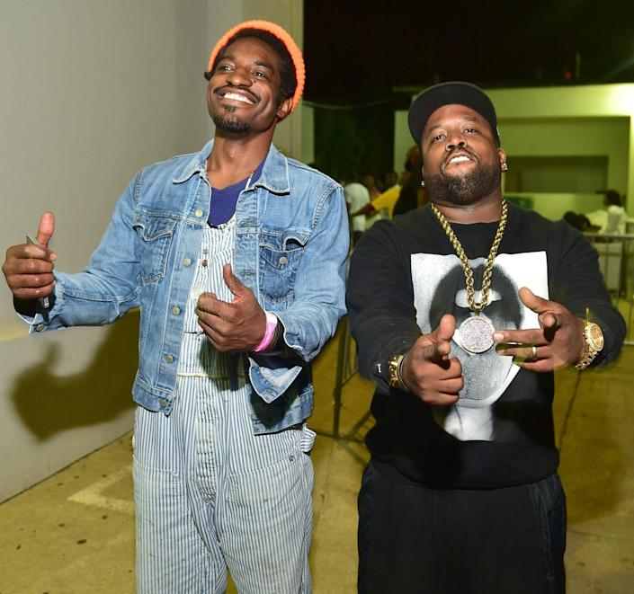 Two rappers pose for a photo in a hallway.