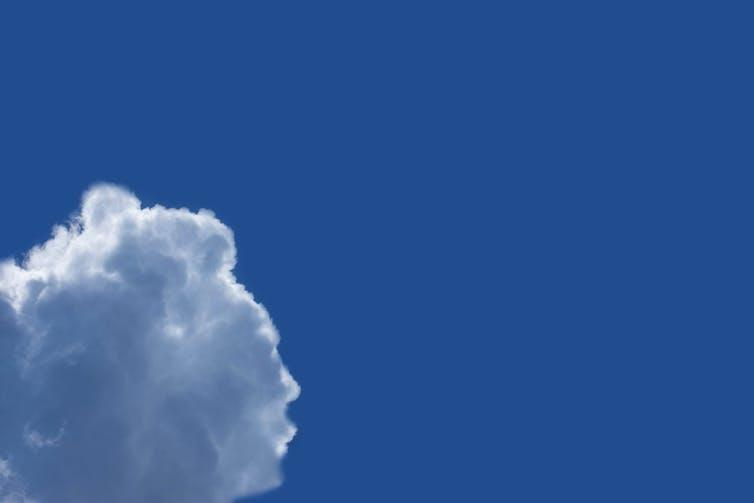 A cloud shaped like the profile of a face in a blue sky