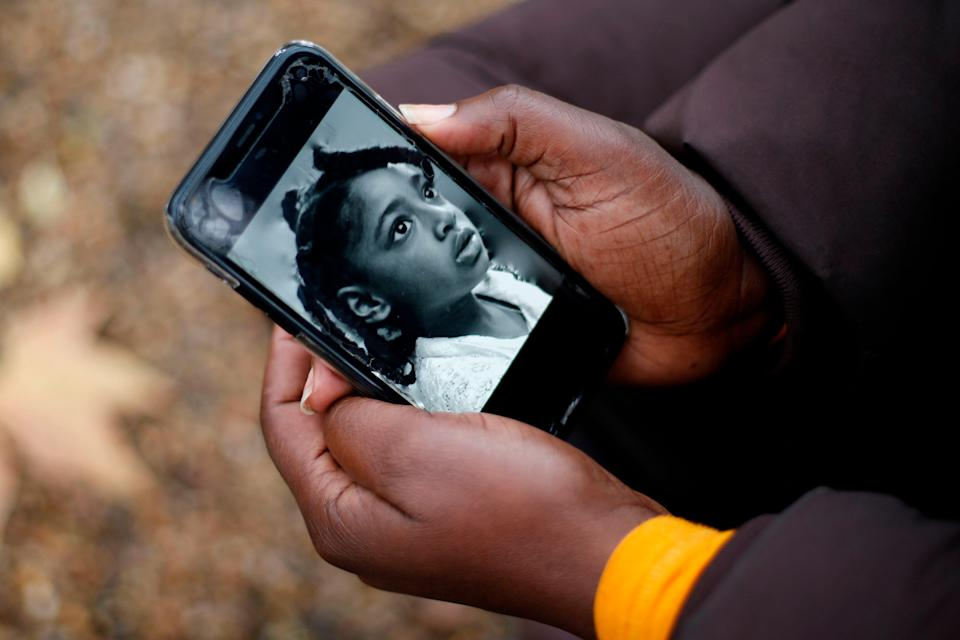 Rosamund Adoo-Kissi-Debrah holds her mobile phone displaying a photograph of her daughter EllaAFP/Getty