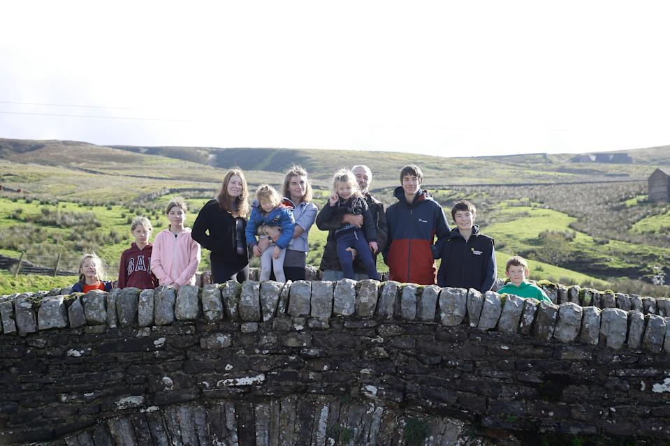 Amanda and Clive Owen with their children Annas, Violet, Edith, Raven, Clemmy, Nancy, Reuben, Miles, and Sidney outside on Ravenseat Farm