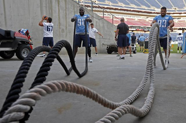 Tennessee Titans defensive linemen Antonio Johnson (90) and Mike Martin (93) work out with heavy ropes in a tunnel at LP Field during NFL football training camp Saturday, Aug. 2, 2014, in Nashville, Tenn. (AP Photo/Mark Humphrey)