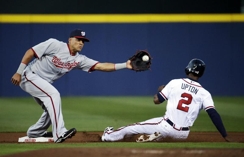 Atlanta Braves' B. J. Upton, right, is caught stealing second base as Washington Nationals' Ian Desmond, left, makes the catch for an out in the first inning of a baseball game, Friday, April 11, 2014, in Atlanta. (AP Photo/David Goldman)