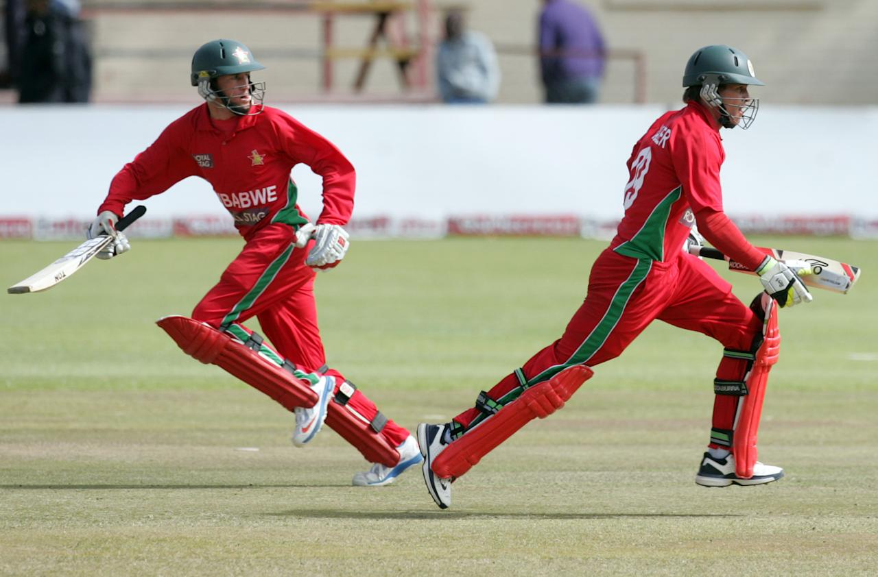Zimbabwe's captain Brendan Taylor (R) runs next to teammate Sean Williams during the 5th and final game of the cricket ODI series between Zimbabwe and India at the Queens Sports Club in Harare, on August 3, 2013. AFP PHOTO / JEKESAI NJIKIZANA        (Photo credit should read JEKESAI NJIKIZANA/AFP/Getty Images)