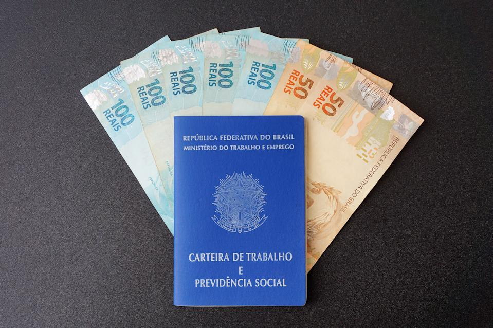 Brazilian work card with Brazilian Real banknotes on black background.