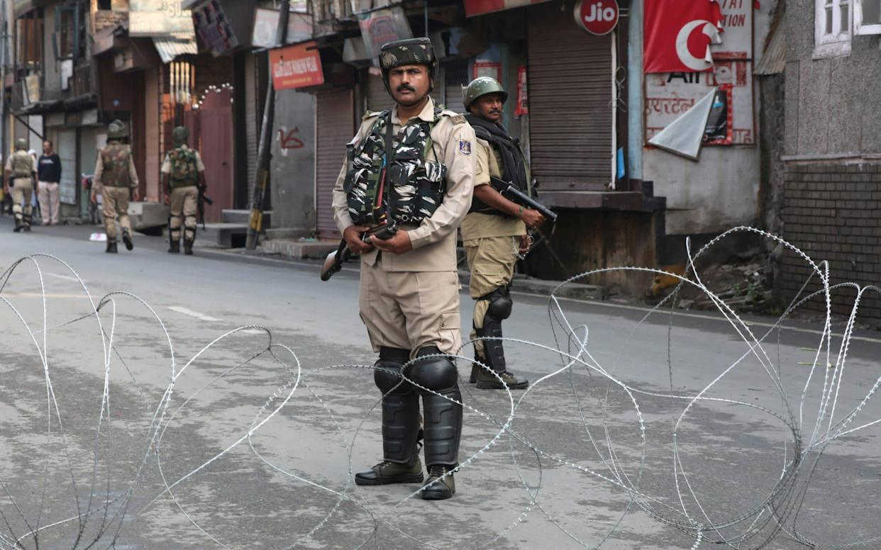 Paramilitary soldiers stand guard near a barbed wire barriacde during curfew in Srinagar, the summer capital of Indian Kashmir - REX
