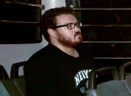 FILE PHOTO: Rurik George Caton Jutting, a British banker charged with two counts of murder after police found the bodies of two women in his apartment, sitting in the back row of a prison bus as he arrives at the Eastern Law Courts in Hong Kong November 24, 2014. REUTERS/Bobby Yip/File Photo