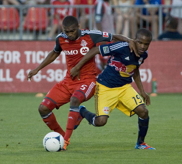 Toronto FC Ashtone Morgan, left, battles for the ball against New York Red Bulls Dane Richards, right, during second half MLS soccer action in Toronto on Saturday June 30, 2012. THE CANADIAN PRESS/Aaron Vincent Elkaim