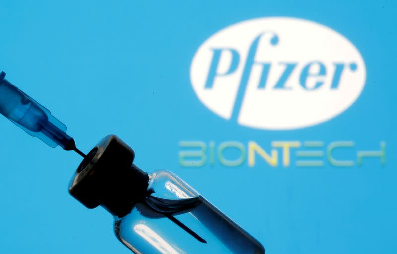 FILE PHOTO: Vial and sryinge are seen in front of displayed Pfizer and Biontech logo