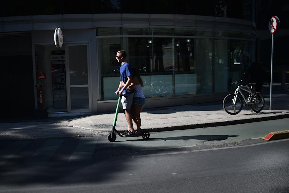 A couple rides a rented electric scooter along Reforma Avenue in Mexico City on February 28, 2019. - The model installed recently in several cities of Latin America focuses on the fight against pollution and traffic congestion. These problems, exacerbated in the region, make a fertile ground for this business that is expanding at great speed. (Photo by RODRIGO ARANGUA / AFP)        (Photo credit should read RODRIGO ARANGUA/AFP via Getty Images)