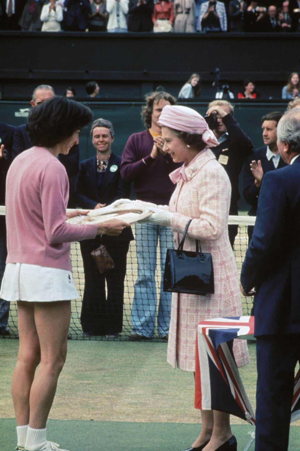 <p><strong>1977</strong> The Queen wore a pink-and-white ensemble to the women's final in 1977, before presenting the trophy.</p>