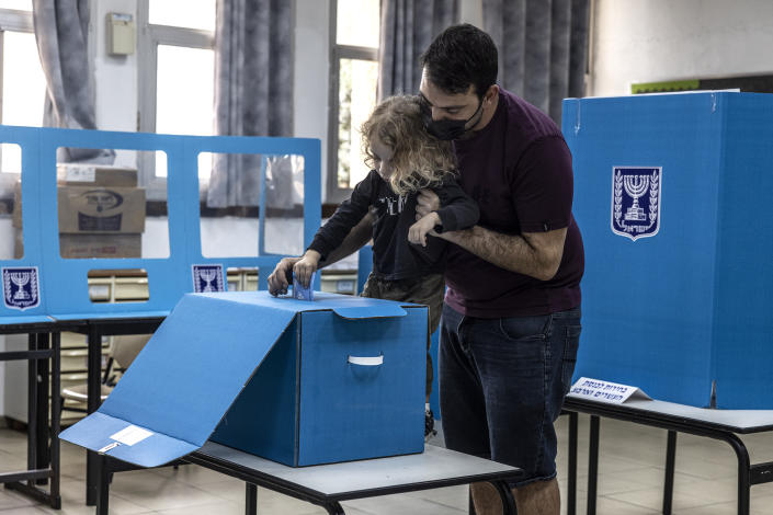 Israelis votes for Israel's parliamentary election at a polling station in the city of Yavne, Israel, Tuesday, March. 23, 2021. Israel is holding its fourth election in less than two years. (AP Photo/Tsafrir Abayov)