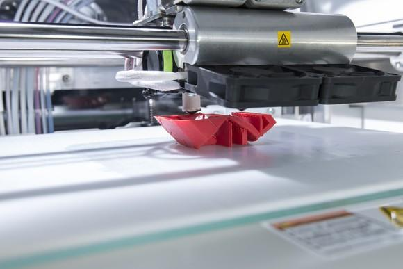 Industrial 3D printer printing a red plastic object.
