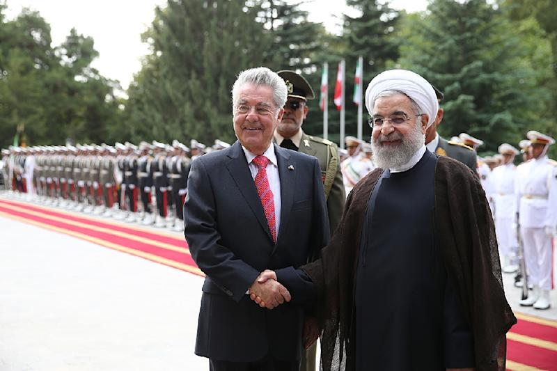 A photo provided by the office of Iranian President Hassan Rouhani shows him (R) shaking hands with his Austrian counterpart Heinz Fischer during a welcome ceremony in Saad Abad palace at Tehran on September 8, 2015
