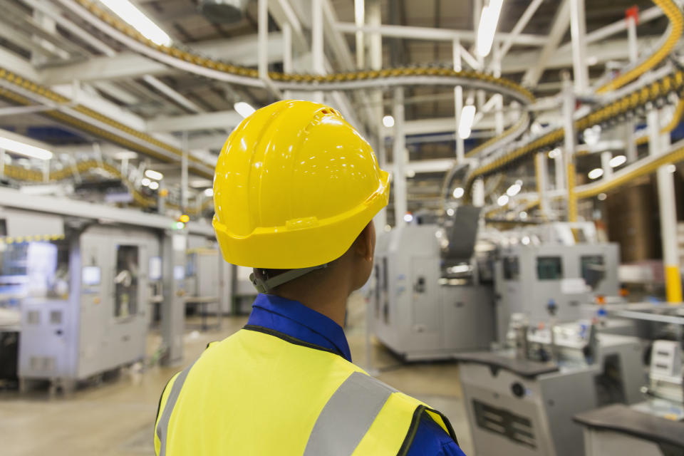 Worker in hard-hat watching printing press conveyor belts and machinery in printing plant