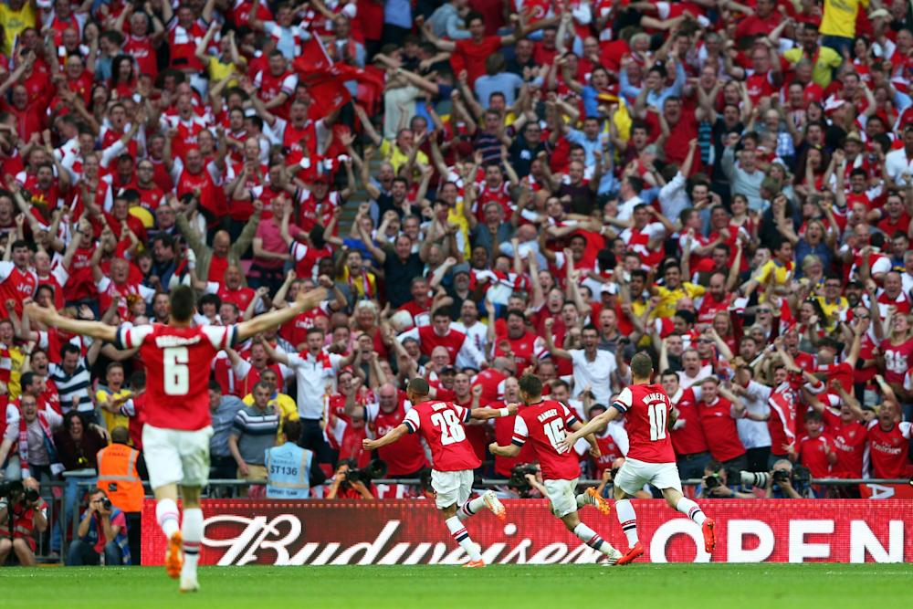 Aaron Ramsey of Arsenal (16) celebrates with fans and team mates as he scores their third goal during the FA Cup final 2014