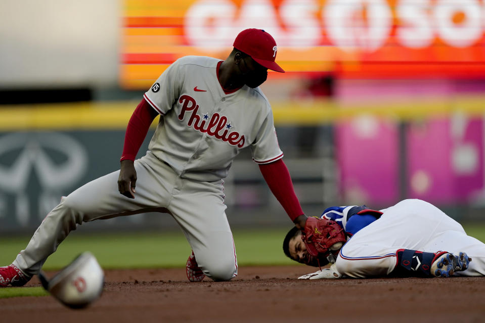 Atlanta Braves' Travis d'Arnaud (16) is safe at second base with a double as Philadelphia Phillies shortstop Didi Gregorius (18) applies the late tag in the first inning of a baseball game Sunday, April 11, 2021, in Atlanta. (AP Photo/John Bazemore)