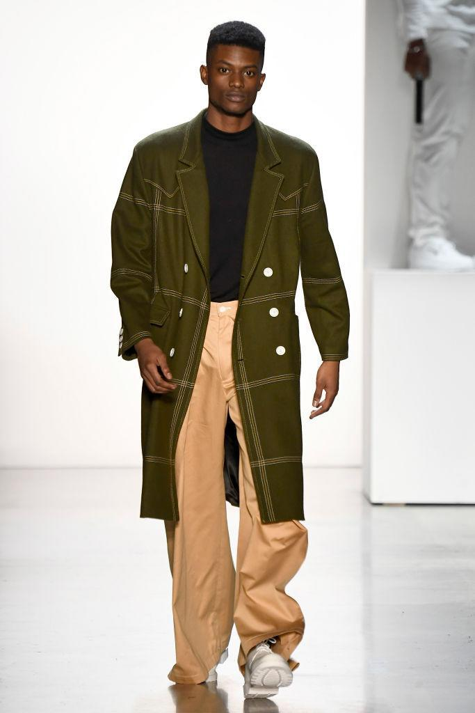 <p>Model wears a hunter green coat, black top, and tan trousers at the Pyer Moss FW18 show. (Photo: Getty) </p>