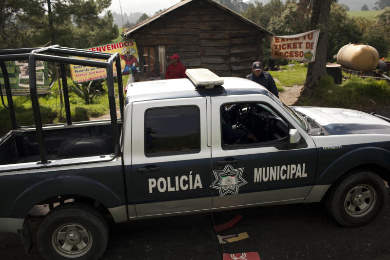 A municipal police truck arrives to the entrance of Rancho la Mesa, which leads to Rancho La Negra in Tlalmanalco, Mexico, Thursday, Aug. 22, 2013. Mexican authorities said Thursday that they have found a mass grave east of Mexico City and are testing to determine if it holds some of the 12 people who vanished from a bar in an upscale area of the capital nearly three months ago. (AP Photo/Ivan Pierre Aguirre)