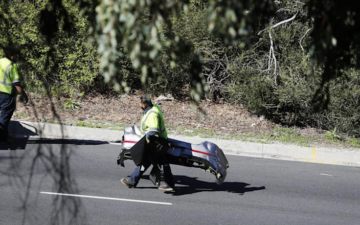 Debris from the vehicle is carried from the scene as a crane is used to pick up a Genesis GV80 SUV driven by US golfer Tiger Woods at the scene of a single-vehicle crash in Rancho Palos Verdes, California - EPA