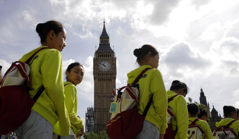 Chinese tourists walk past the Palace of Westminster and the Queen Elizabeth Tower in London, Monday, Aug. 14, 2017. Big Ben will fall silent next week in London as a major restoration project gets underway. The bongs of the iconic bell will be stopped on Aug. 21 to protect workers during a four-year, 29-million-pound ($38 million) conservation project that includes repair of the Queen Elizabeth Tower, which houses Big Ben and its clock.(AP Photo/Alastair Grant)