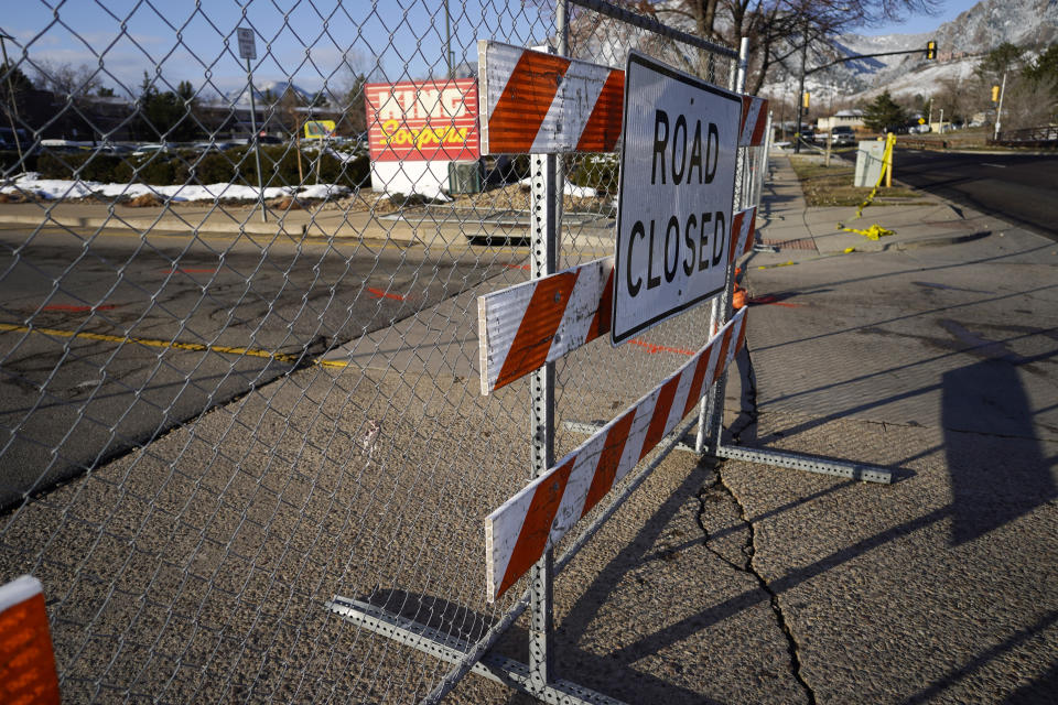 A road closed sign stands along a makeshift fence put up around the parking lot outside a King Soopers grocery store where a mass shooting took place a day earlier in Boulder, Colo., Tuesday, March 23, 2021. (AP Photo/David Zalubowski)