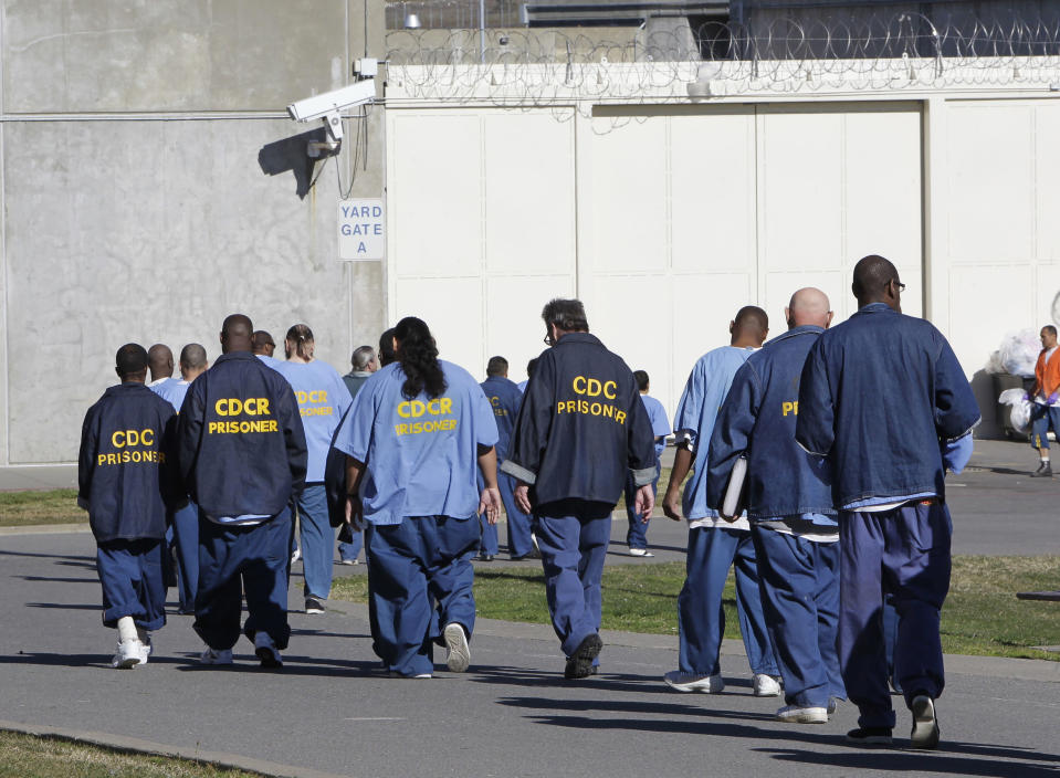 FILE - In this Feb. 26, 2013, file photo, inmates walk through the exercise yard at California State Prison Sacramento, near Folsom, Calif. The California Labor and Workforce Development Agency confirmed Tuesday, Dec. 1, 2020, that California has sent about $400 million in unemployment benefits to state prison inmates. In all records show 31,000 inmates have applied for benefits and about 20,800 were paid $400 million. A group of local and federal prosecutors said 133 inmates on death row were named in claims. (AP Photo/Rich Pedroncelli, File)