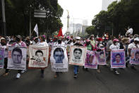 Supporters and relatives of the 43 missing university students hold placards with photos of their loved ones as they march on the seventh anniversary of their disappearance, in Mexico City, Sunday, Sept. 26, 2021. Relatives continue to demand justice for the Ayotzinapa students who were allegedly taken from the buses by the local police and handed over to a gang of drug traffickers. (AP Photo/Marco Ugarte)