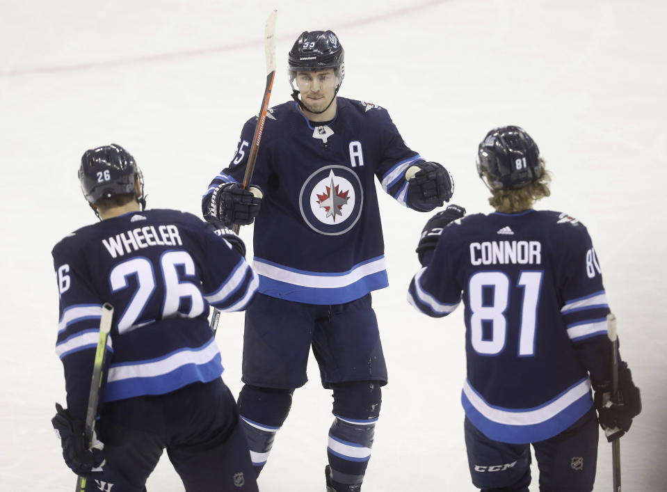 Winnipeg Jets' Blake Wheeler (26), Mark Scheifele (55) and Kyle Connor (81) celebrate after Connor scored an empty-net goal against the Vegas Golden Knights during the third period of an NHL hockey game Tuesday, Jan. 15, 2019, in Winnipeg, Manitoba. (Trevor Hagan/The Canadian Press via AP)