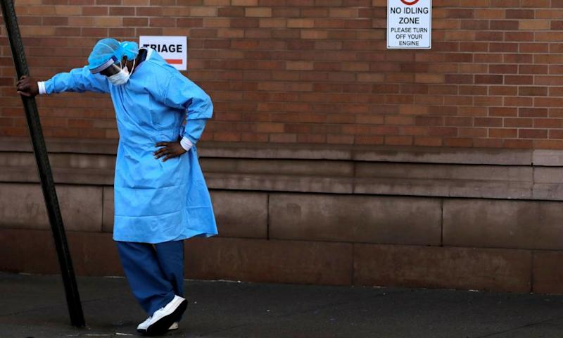 A healthcare worker takes a break outside the emergency center at Maimonides medical center in Brooklyn, New York.